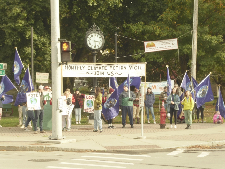 Protesters hold signs and flags at the climate vigil in Canton.