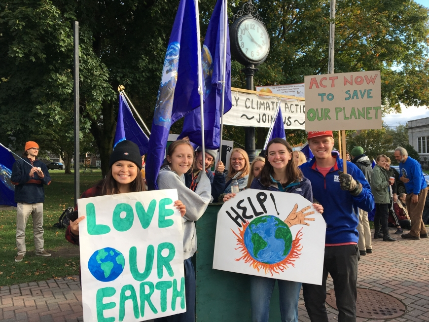 SLU students hold signs protesting climate change.