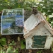 White paper-birch covered fairy house resting against log with poster nailed to log next to it