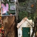Image of a white birch fairy house nestled against a rock with a poster attached to tree