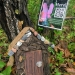 Image of a brown fairy house at the base of trees with a poster attached to a tree